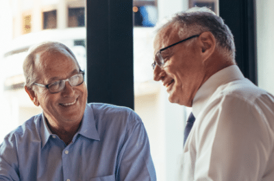 Two elderly men engaged in conversation.